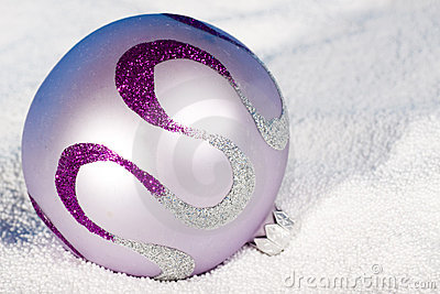 Tender lilac Christmas bauble on to snow.