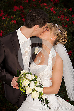 Tender wedding kiss red roses