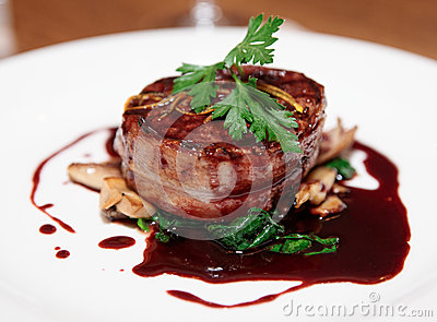Tenderloin steak wrapped in bacon with red sauce