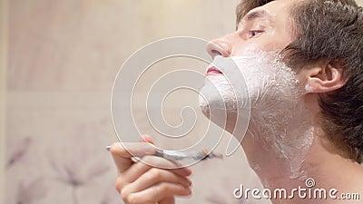 Tener la cara del hombre afeitándose espuma almacen de video
