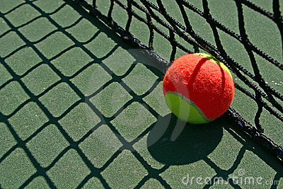 Tennis ball besides the net