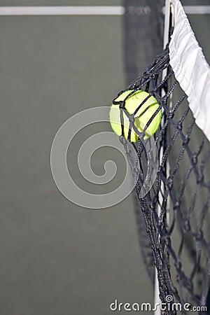 Tennis ball hitting the net on a court