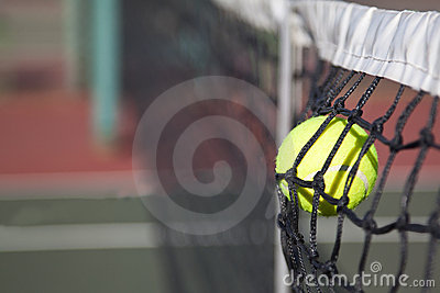 Tennis ball hitting the net on a court