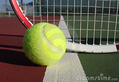 Tennis ball and racquet in background