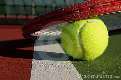 Tennis ball and racquet on a court