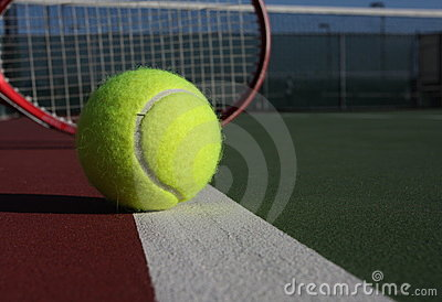 Tennis ball and racquet on court