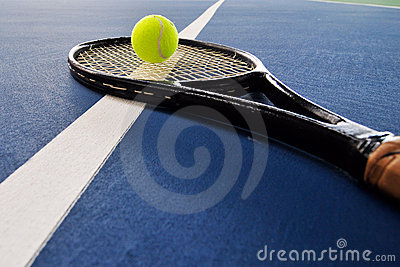 Tennis ball and racquet on a court line