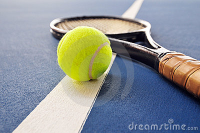 Tennis ball and racquet on a court line