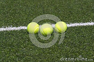 Tennis balls lays on grass court line
