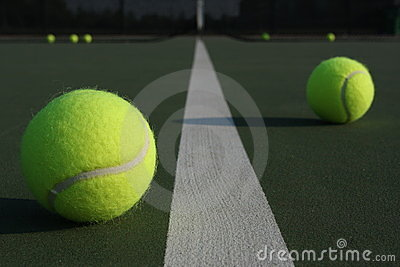 Tennis balls straddling the court line