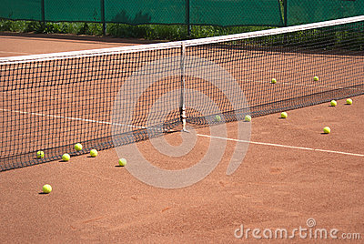 Tennis court and yellow ball before net