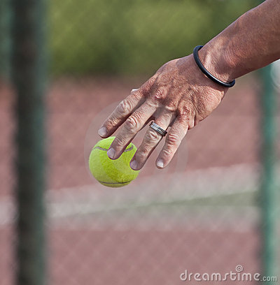 Tennis player bouncing  ball on court