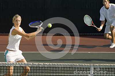 Tennis Player Hitting Ball With Partner Standing In Background