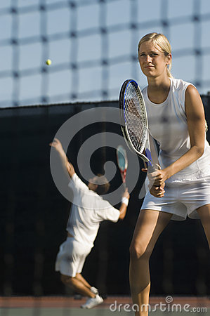 Tennis Player Holding Racket With Partner Serving Ball In Background