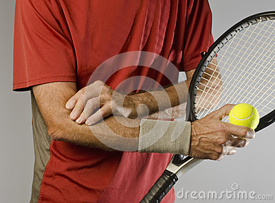 Tennis player massaging elbow