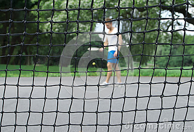 Tennis player seen through the net