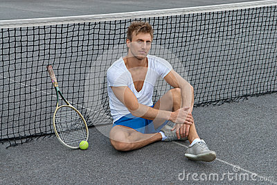 Tennis player sitting besides the net