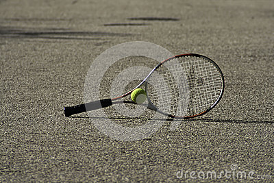 Tennis racket and ball on the ground