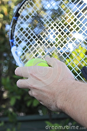Tennis racquet and ball in hands