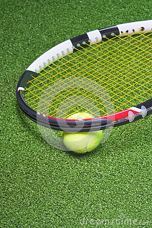 Tennis Racquet with Ball over Green Artificial Grass