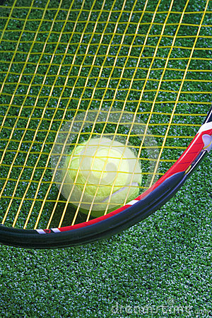 Tennis Racquet with Ball over Green Artificial Grass
