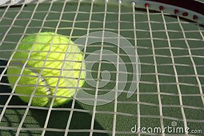 Tennis racquet with a tennis ball beneath