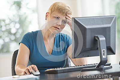 Tensed Businesswoman Using Computer At Desk