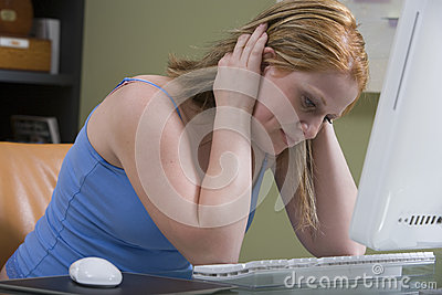 Tensed Woman Sitting At Computer Desk