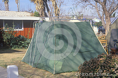 A tent set up in a yard housing people Editorial Stock Photo