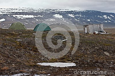 Tents and hut in tundra in the Svalbard