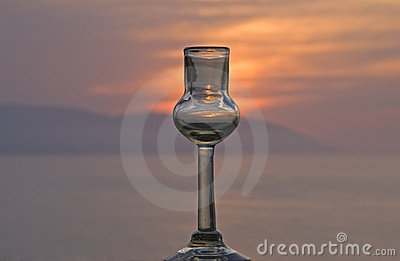 Tequila shot glass with sunset an ocean background