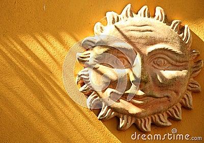 Terakotowy uśmiechnięty słońce na ścianie