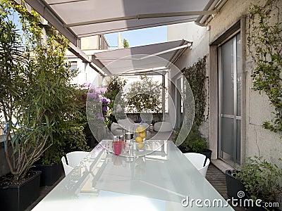 arredamento terrazzo terrazo moderno : Terrazzo moderno con una tabella di vetro fra le piante ed i fiori.