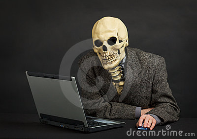 Terrible skeleton sits at black office with laptop