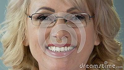 Tevreden hogere vrouwelijke patiënt die na tanden glimlachen die procedure, close-up witten stock videobeelden