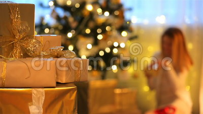 Thème de Noël Les présents, lumières, arbre, jeune femme ouvre des cadeaux banque de vidéos
