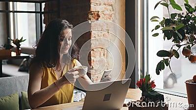 Thé potable de jeune femme mignonne utilisant le smartphone dans le sourire de détente de café clips vidéos
