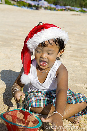 Thai boy with christmas hat on beach