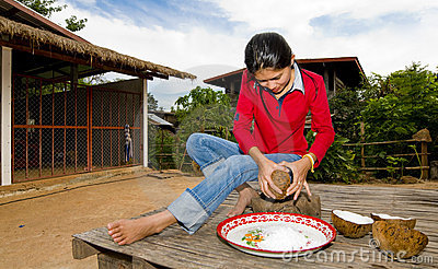 Thai girl removing coconut meat from shell