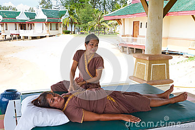 Thai masseuse at work on the beach Editorial Stock Image