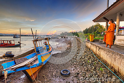 Thai monk meditating at sunrise on the harbor Editorial Stock Photo