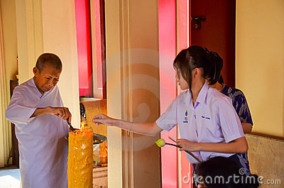Thai schoolgirl helping a nun lighting giant c Editorial Stock Photo