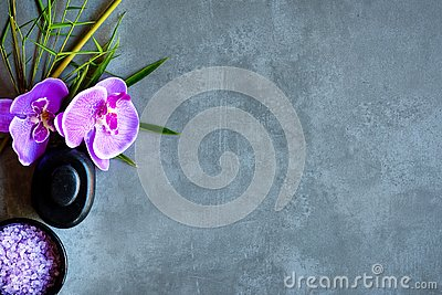 Thai Spa. Top view of hot stones setting for massage treatment and relax with purple orchid on blackboard with copy space. Stock Photo
