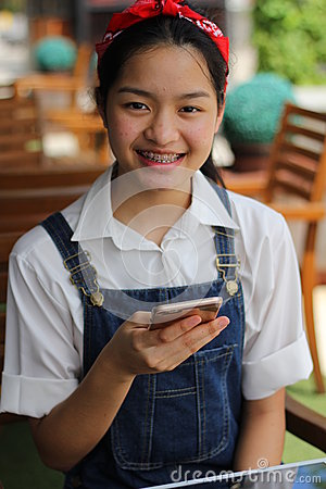 Free Thai Student Teen Beautiful Girl Using Her Smart Phone And Smile. Royalty Free Stock Image - 56552776