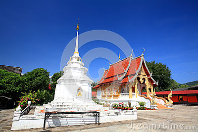Thai white pagoda and temple against blue sky