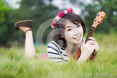 Thai woman lie and hug Ukulele in garden
