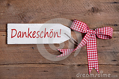 Thank you card with a red checkered ribbon on old wooden board