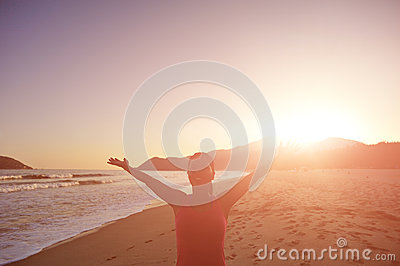 Thankful woman open arms on beach