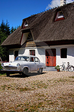 Thatched roof house and car