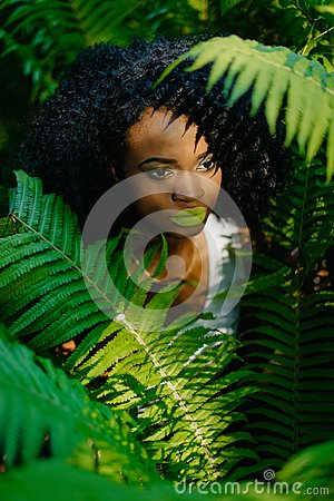 Free The Attractive Pretty African Girl With Green Eyeshadows And Lipstick Is Surrounded By Green Ferns. No Look In Camera Royalty Free Stock Photos - 114526118